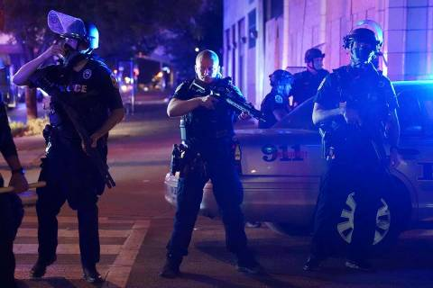 Police stand at an intersection after an officer was shot, Wednesday, Sept. 23, 2020, in Louisv ...