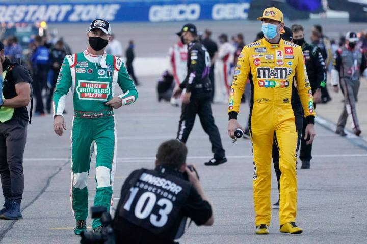 Kevin Harvick, left, and Kyle Busch, right, walk to their cars prior to the start of a NASCAR C ...