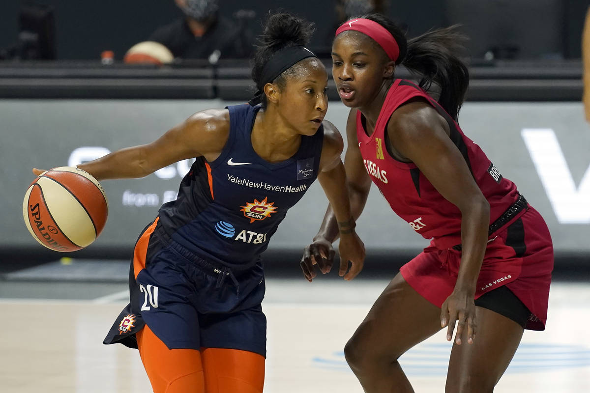 Connecticut Sun guard Briann January (20) drives around Las Vegas Aces guard Jackie Young (0) d ...