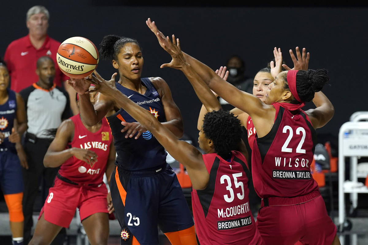 Connecticut Sun forward Alyssa Thomas (25) pass the ball as she is guarded by Las Vegas Aces fo ...
