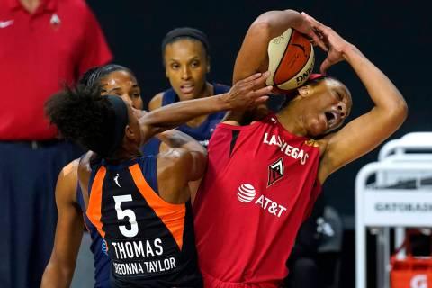 Las Vegas Aces center A'ja Wilson and Connecticut Sun guard Jasmine Thomas (5) battle for a reb ...