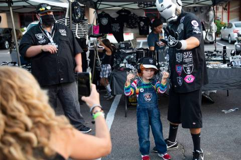Julian Segura, 5, of Los Angeles, poses with Raider Iron Man, of Arizona, at a Raiders party at ...