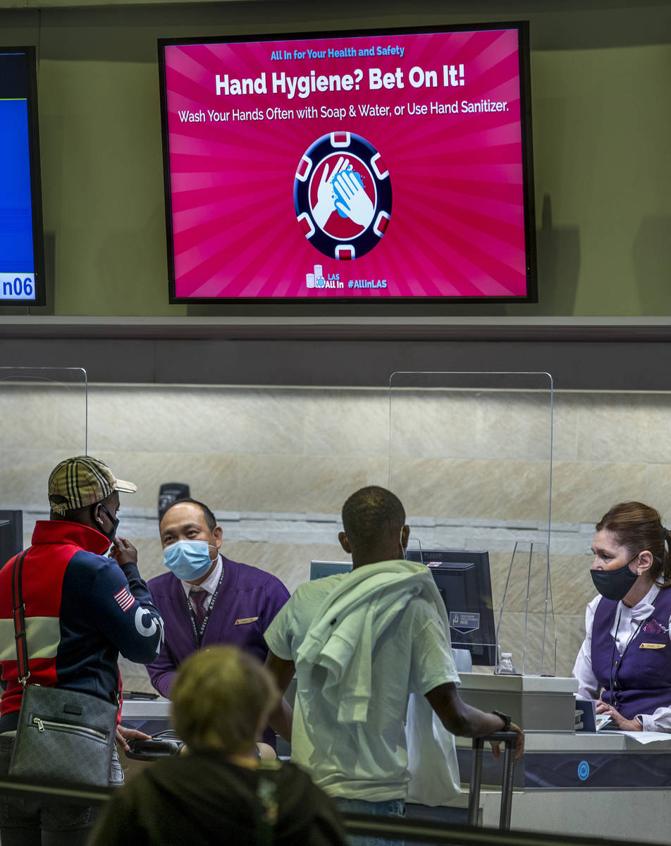 Delta Airlines passengers talk with agents as COVID-19 safety precautions are in place at McCar ...