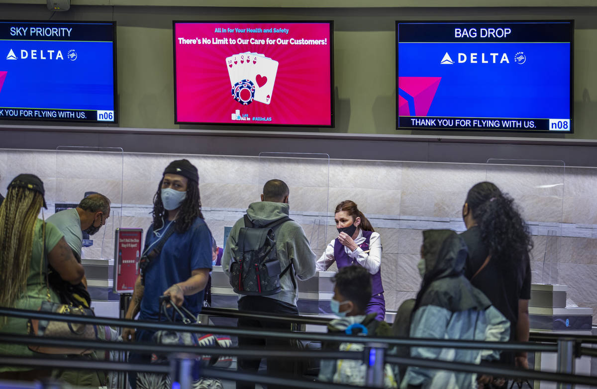 Delta Airlines passengers wait in the check in area as COVID-19 safety precautions are in place ...