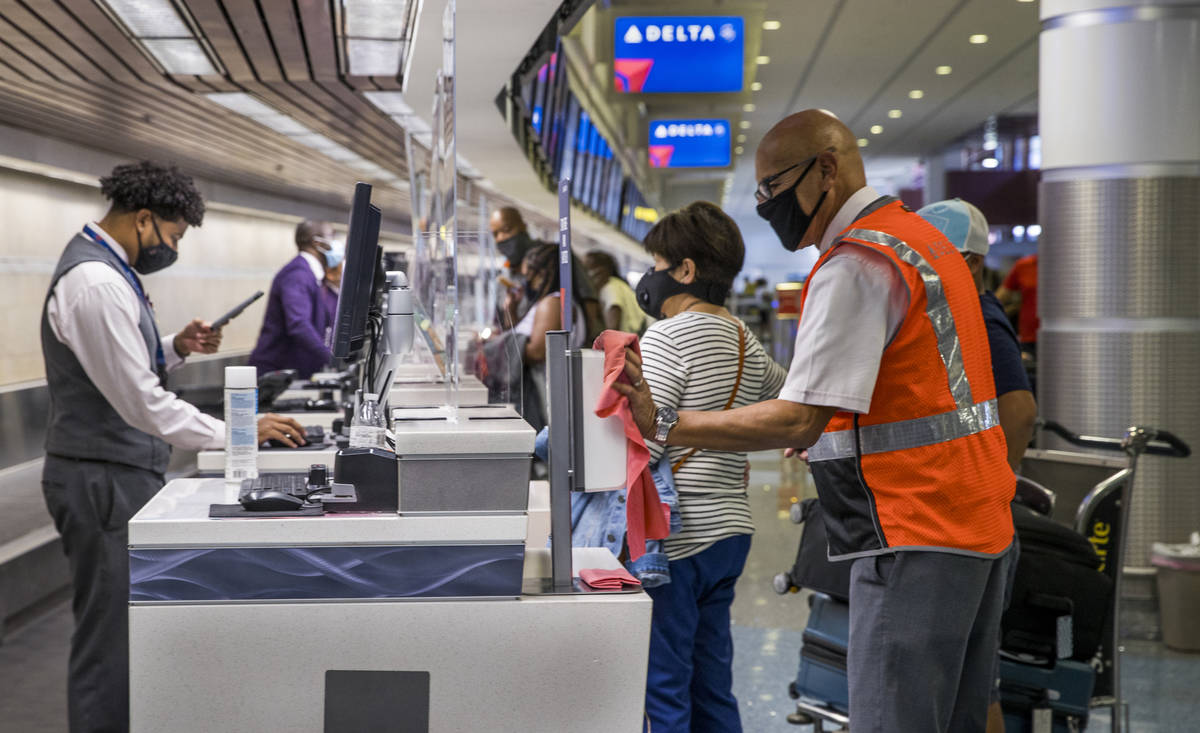 Delta Airlines employee Christopher Castro Jr., right, wipes down various surfaces as customers ...