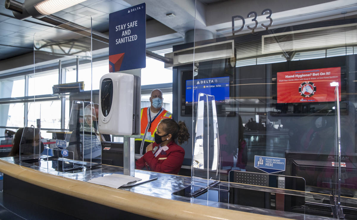 Delta Airlines personnel sit behind plexiglass and have hand sanitizer available at the gates t ...