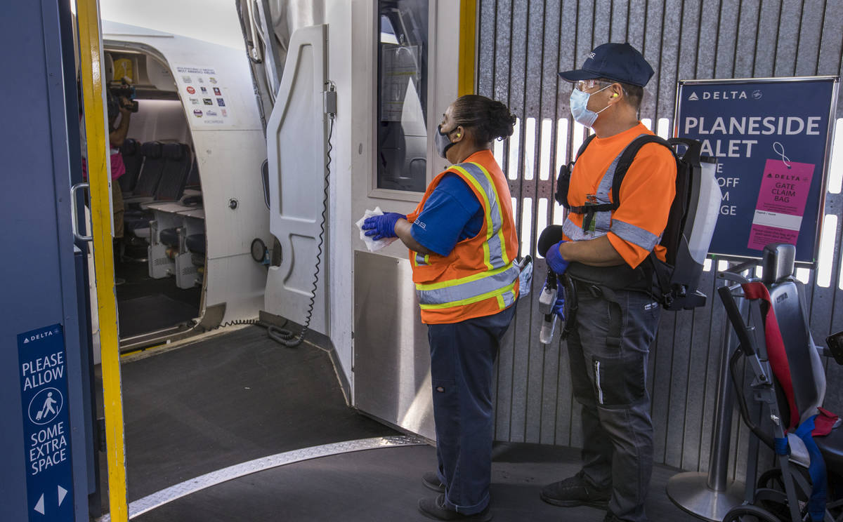 Delta Airlines cleaning personnel prepare to disinfect another airplane as COVID-19 safety prec ...