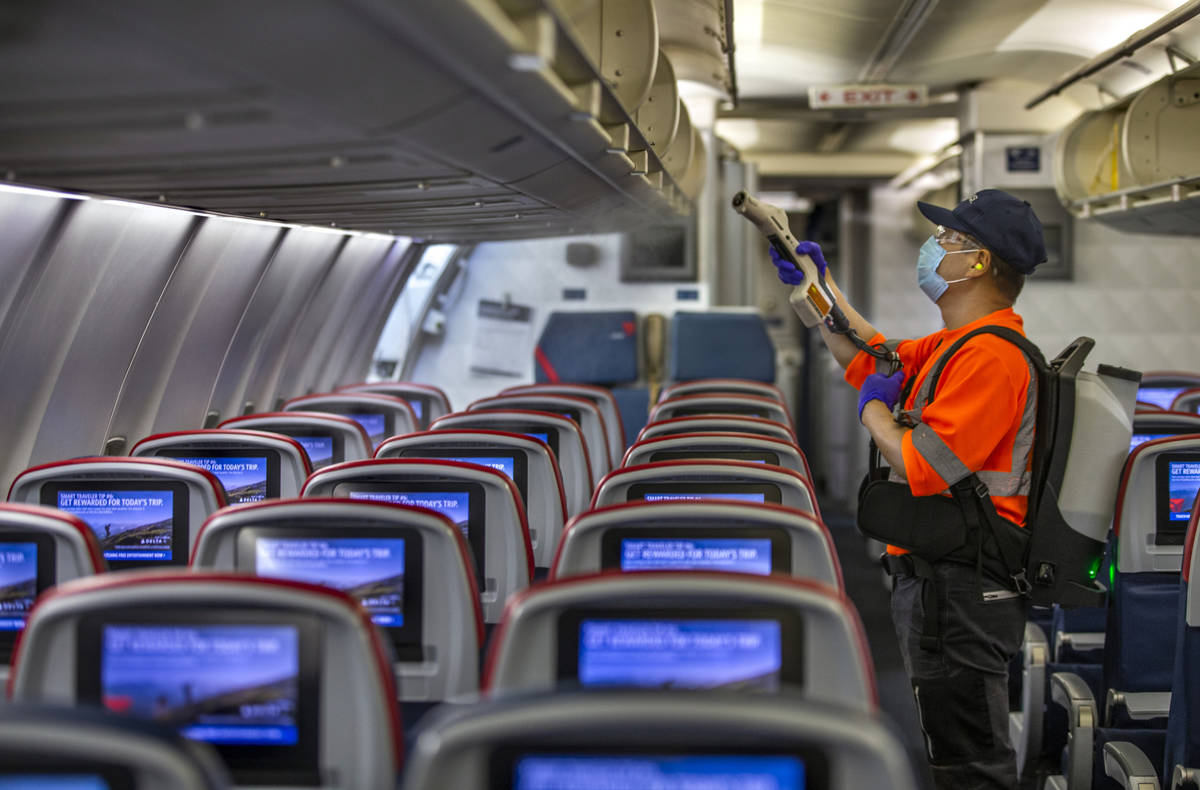Delta Airlines employee Wansik Kim disinfects the interior of another airplane before departure ...