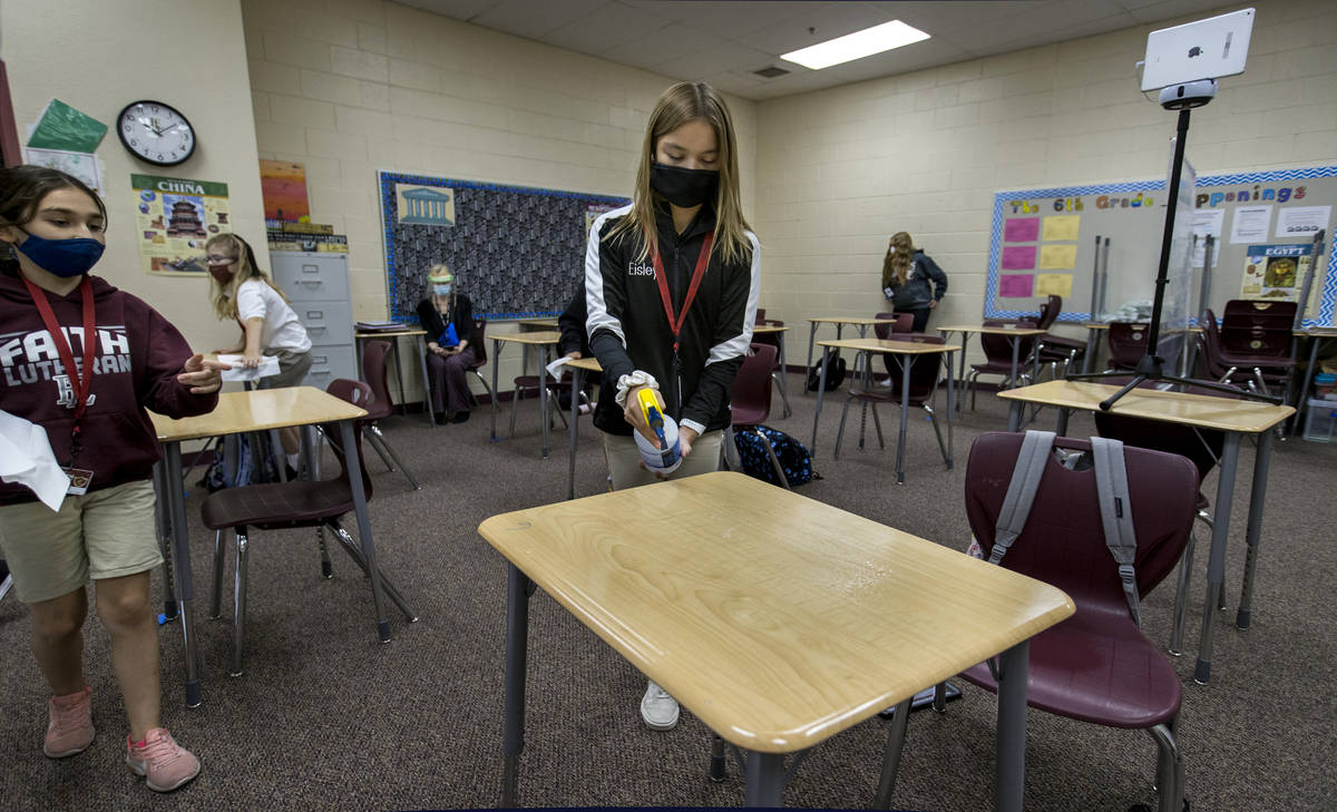 Student Eisley Wheat, 12, center, sprays down a desk for Alyssa Kazemi, 11, as they are cleaned ...