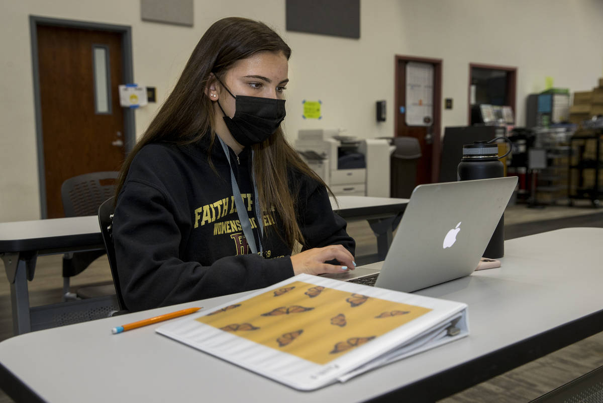Student Tatum Bowers studies in the library with mask and social distancing at Faith Lutheran M ...
