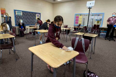 Student Alyssa Kazemi, 11, wipes down her desk with others in teacher Brandon Buskirk's 6th gra ...