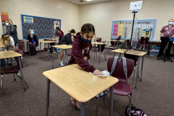 Student Alyssa Kazemi, 11, wipes down her desk with others in teacher Brandon Buskirk's 6th gra ...