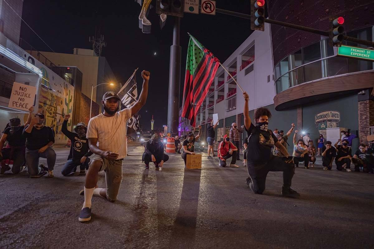 Protesters kneel in silence in honor of Breonna Taylor on Las Vegas Bo., in front of the Fremon ...