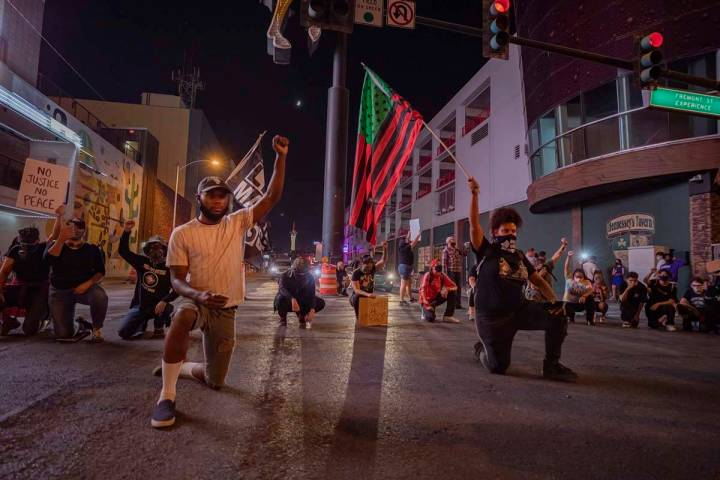 Protesters kneel in silence in honor of Breonna Taylor on Las Vegas Boulevard, in front of the ...
