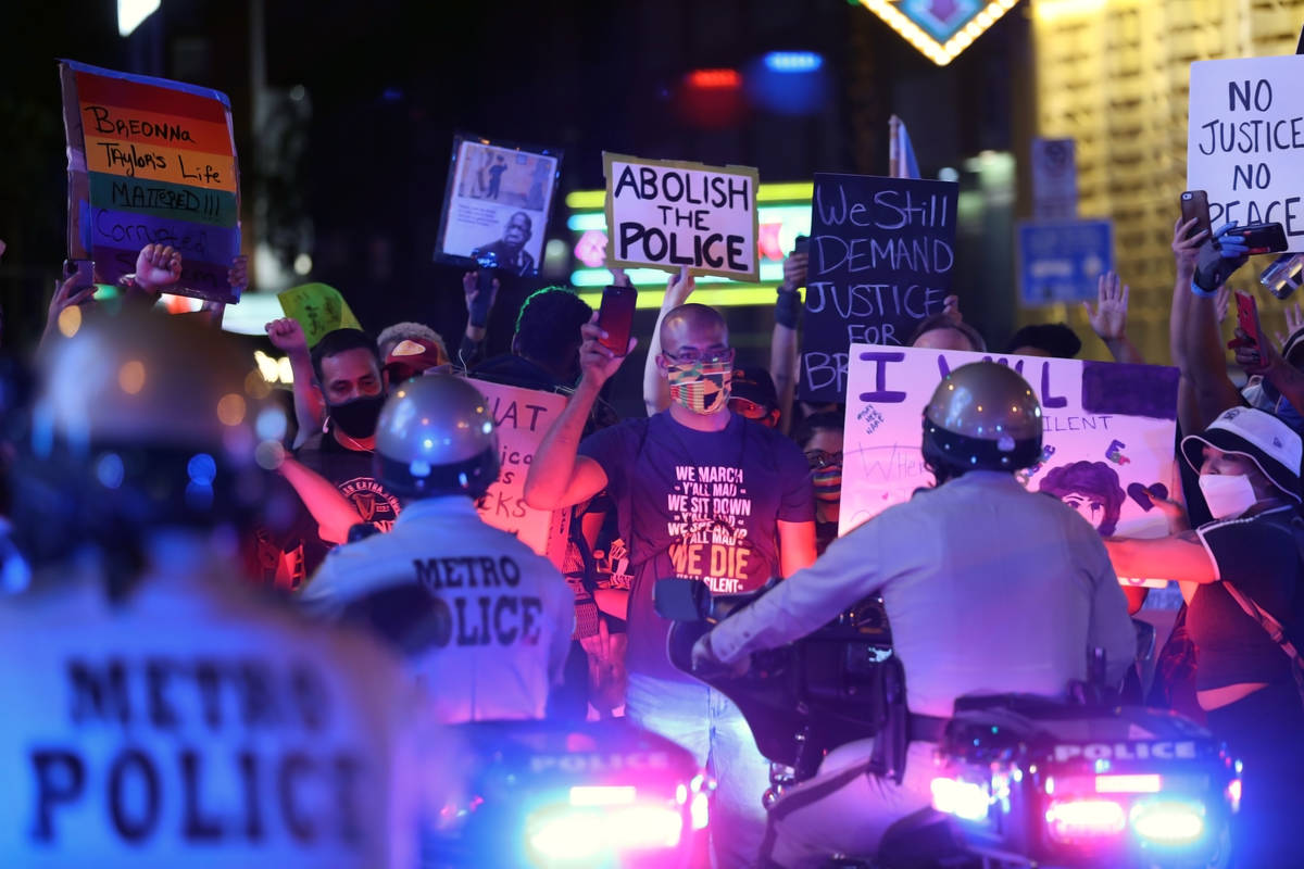Protesters face law enforcement while standing in the middle of Las Vegas Blvd., in front of th ...