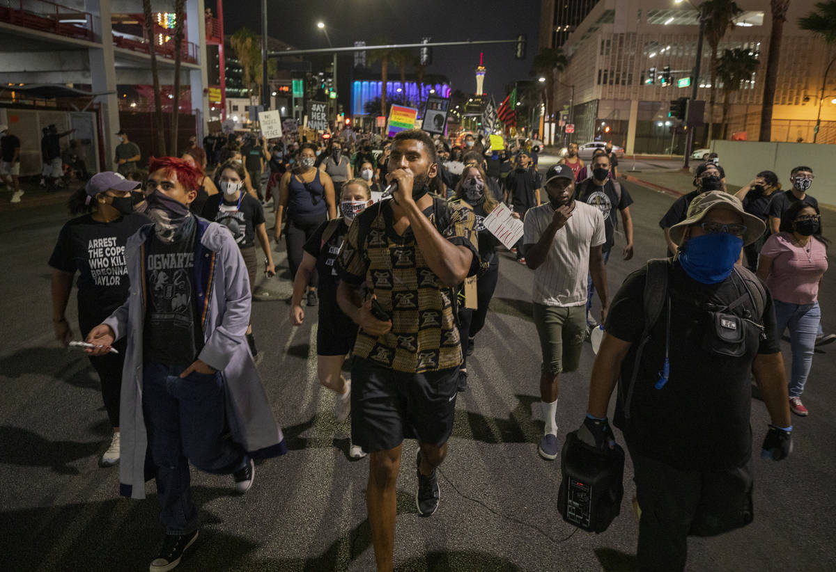 Protesters kneel in silence in honor of Breonna Taylor on Las Vegas Blvd., in front of the Frem ...