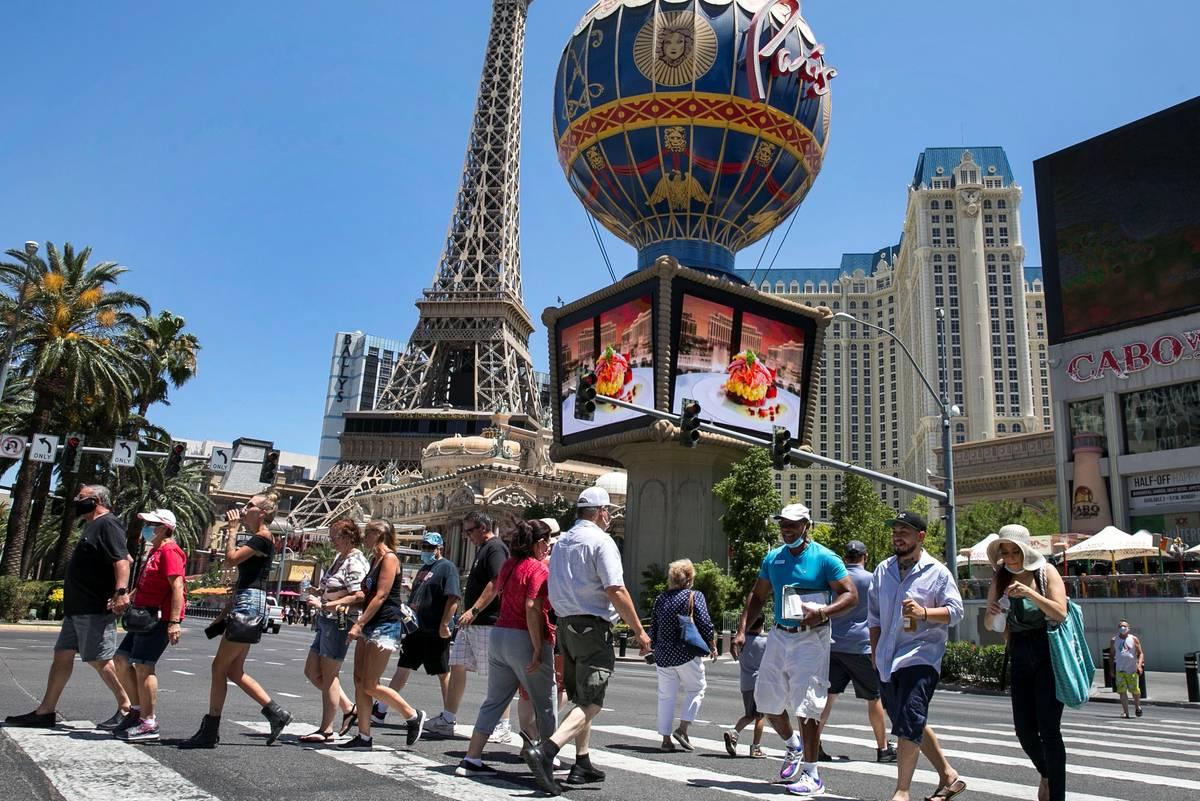 Tourists cross Las Vegas Boulevard near Paris hotel-casino on Friday, July 3, 2020, in Las Vega ...
