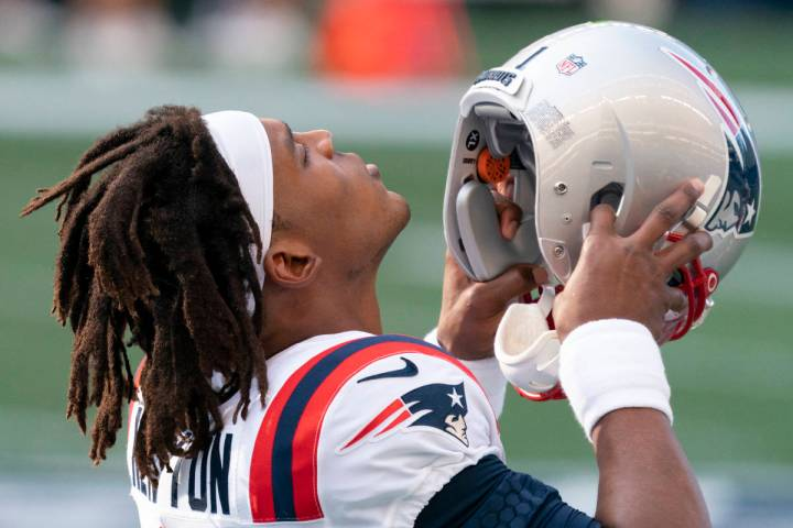New England Patriots quarterback Cam Newton puts on his helmet before an NFL football game agai ...