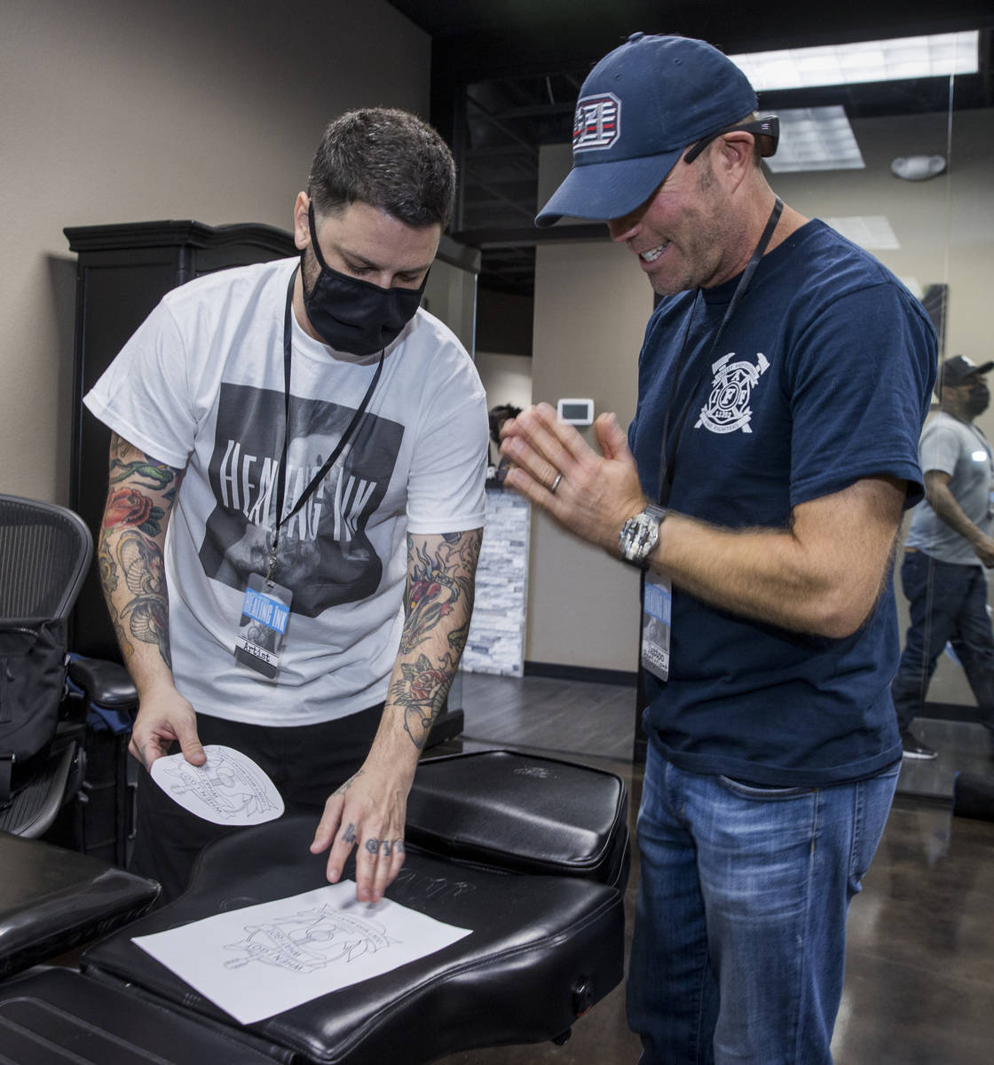Tattoo artist Jim Sylvia, left, shows a sketch to Dean McAuley as Route 91 shooting survivors a ...