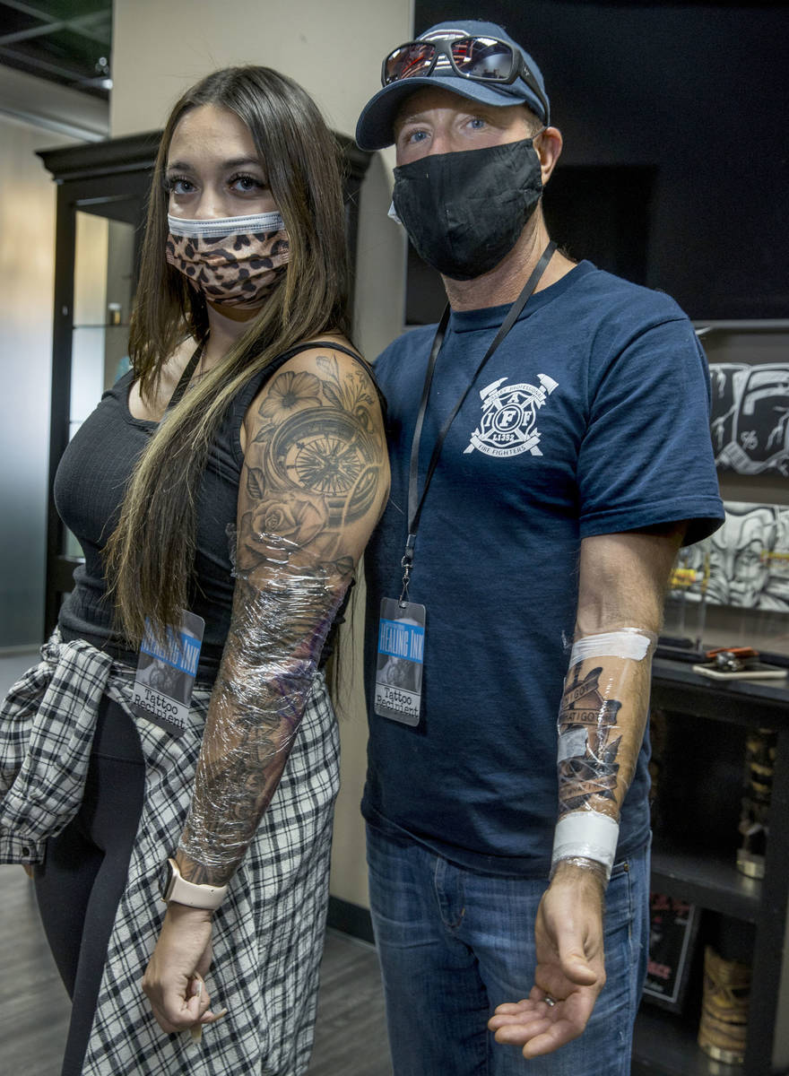 Natalia Baca, left, with Seattle firefighter Dean McAuley show off their finished tattoos as Ro ...