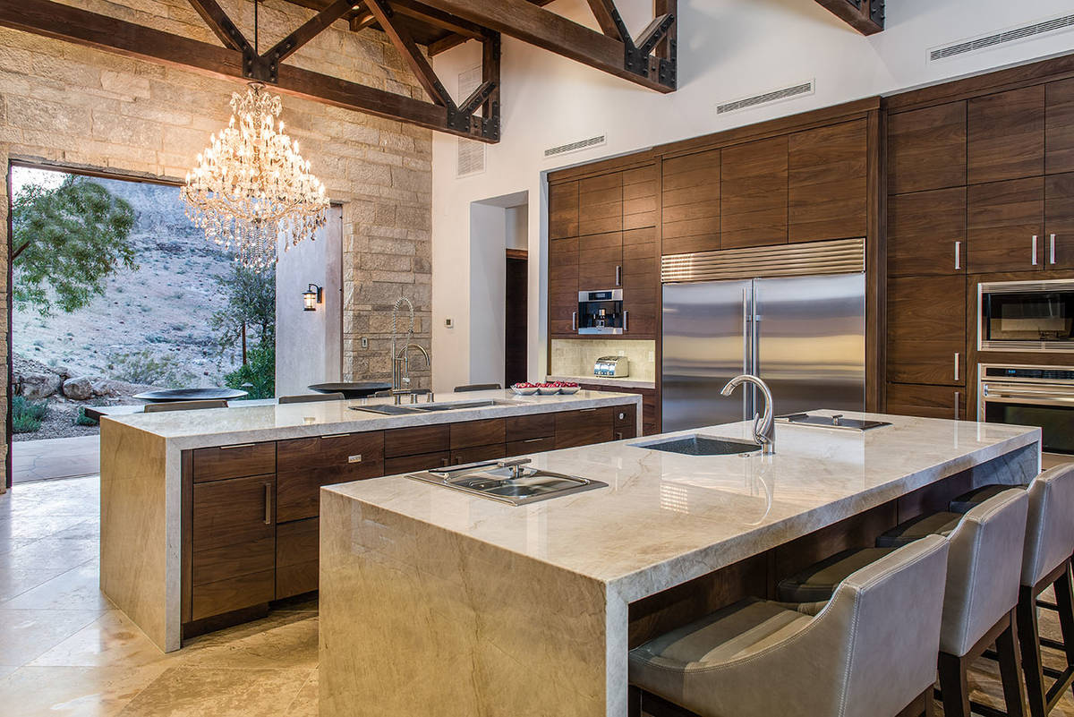 The large kitchen has double islands with seating, upgraded appliances, a modern design and a d ...