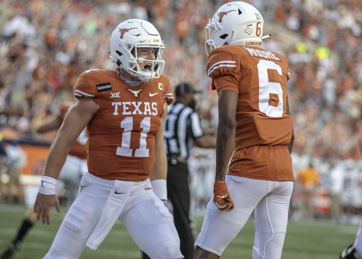 Texas quarterback Sam Ehlinger (11) celebrates with Joshua Moore (6) after a Texas touchdown ag ...