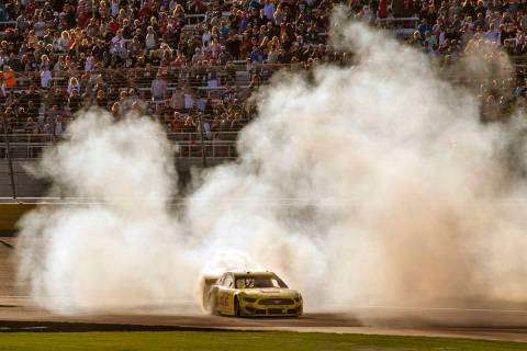 Joey Logano (22) celebrates with a burn out at the finish line following his win in the Pennzoi ...