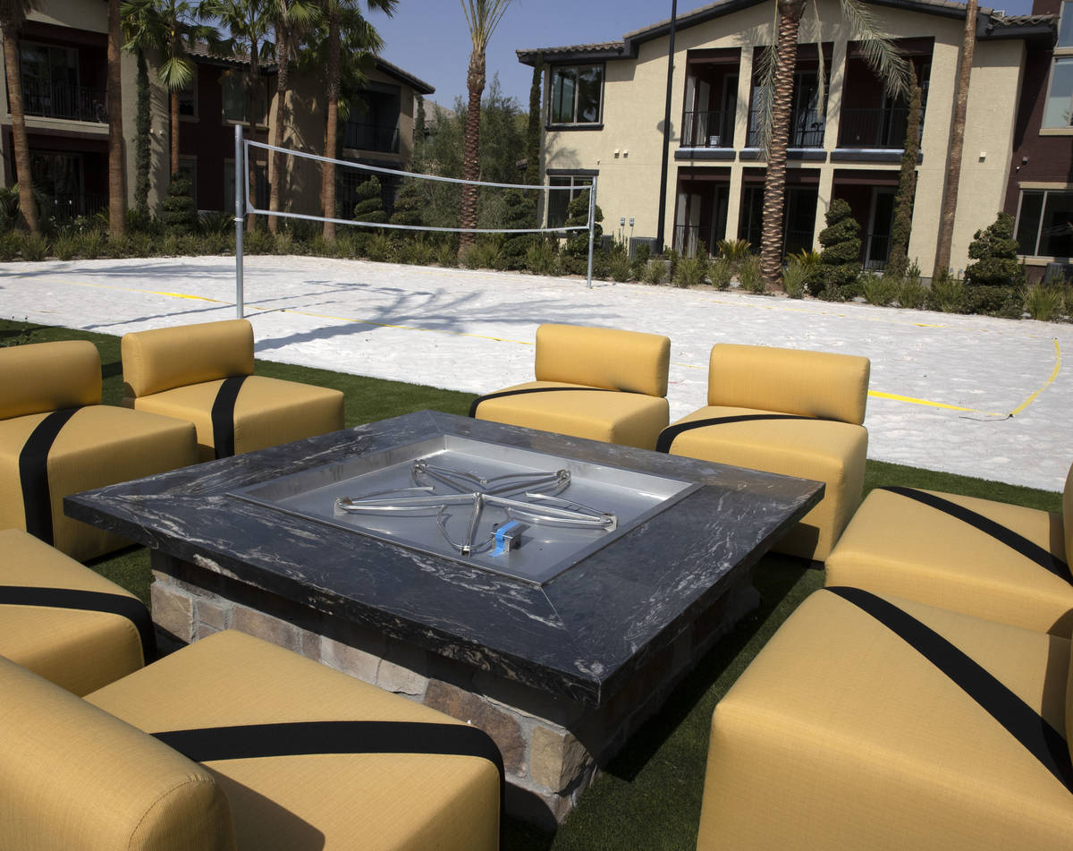 A fire pit and sand volleyball court are seen at the Tuscan Highlands apartment complex under c ...