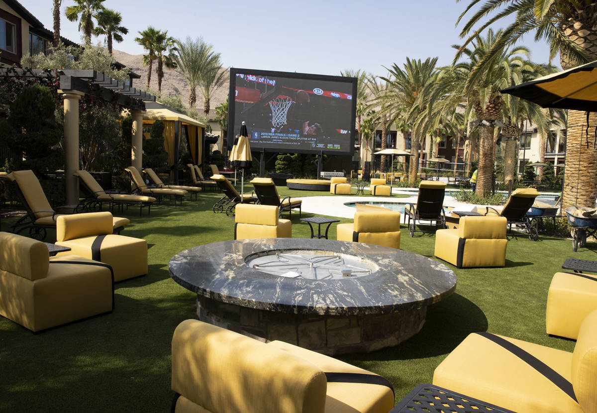 A fire pit and a giant television are seen at a pool area at the Tuscan Highlands apartment com ...