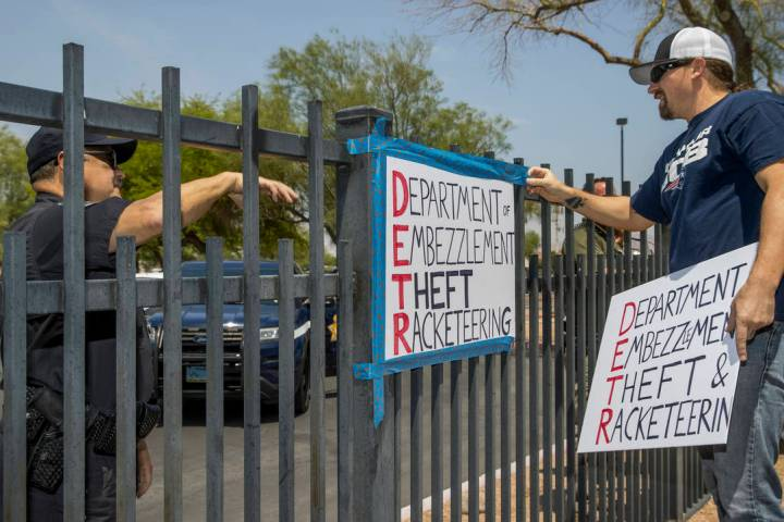 A security guard instructs Jon Berry, right, to take down a sign he attached to a fence in fron ...