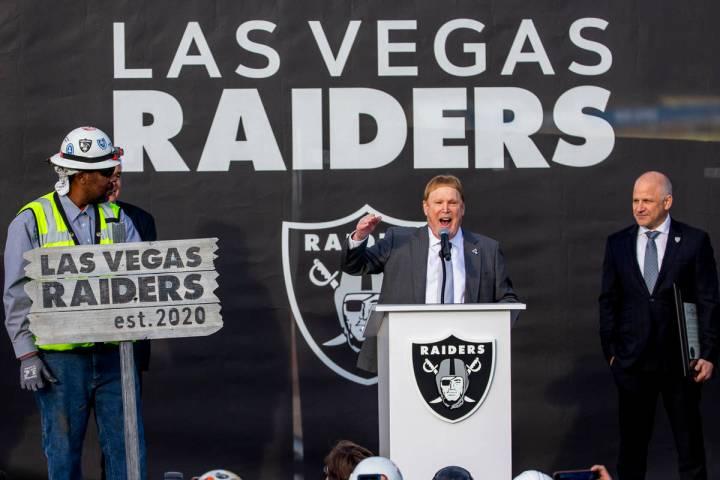 Las Vegas Raiders owner Mark Davis, center, addresses the crowd beside team president Marc Bada ...