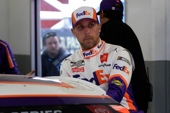 FILE - In this Feb. 14, 2020, file photo, Denny Hamlin climbs into his car as he gets ready to ...