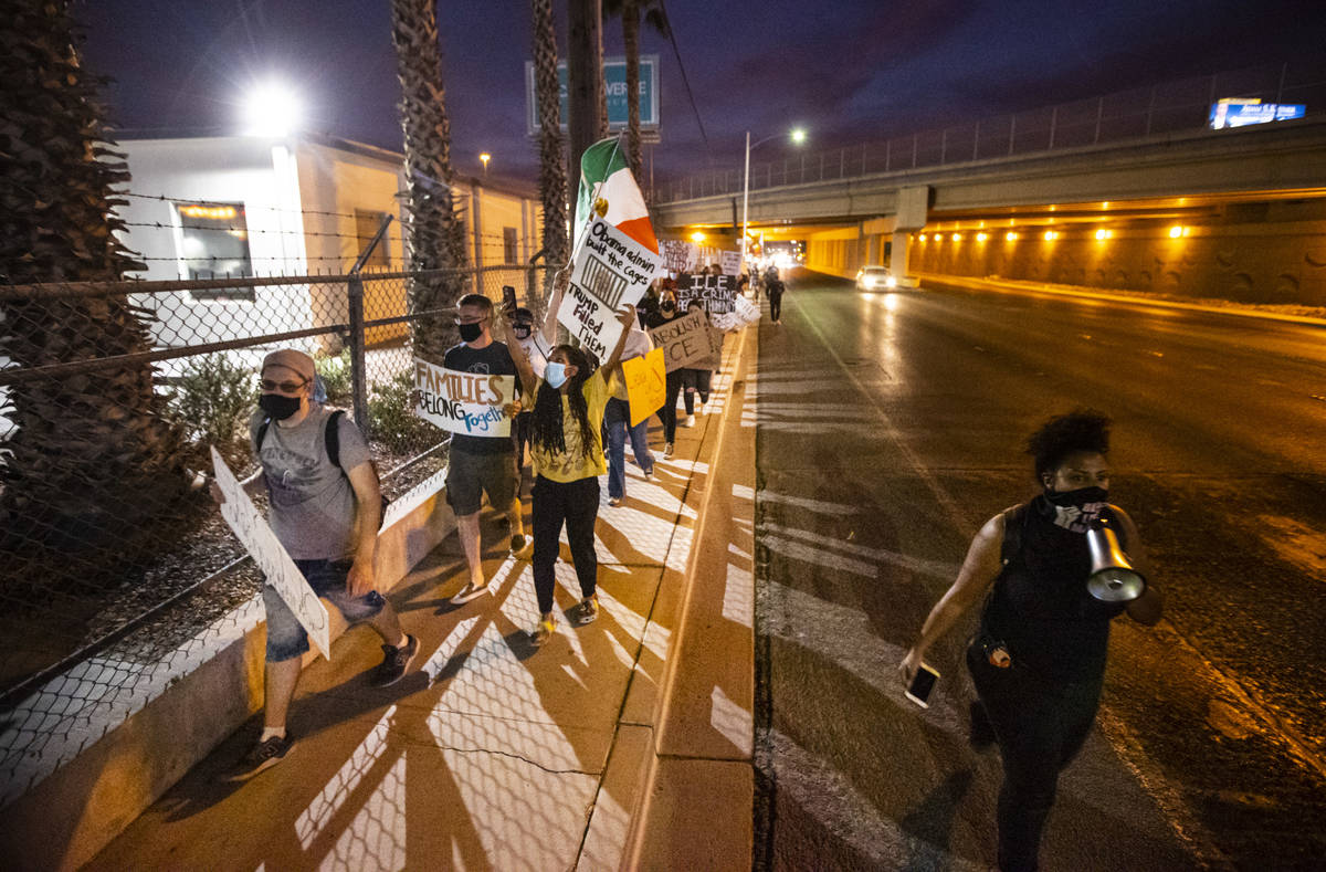 People march down Bonanza Road during a protest against U.S. Immigration and Customs Enforcemen ...