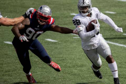 Las Vegas Raiders running back Josh Jacobs (28) turns the corner around New England Patriots li ...