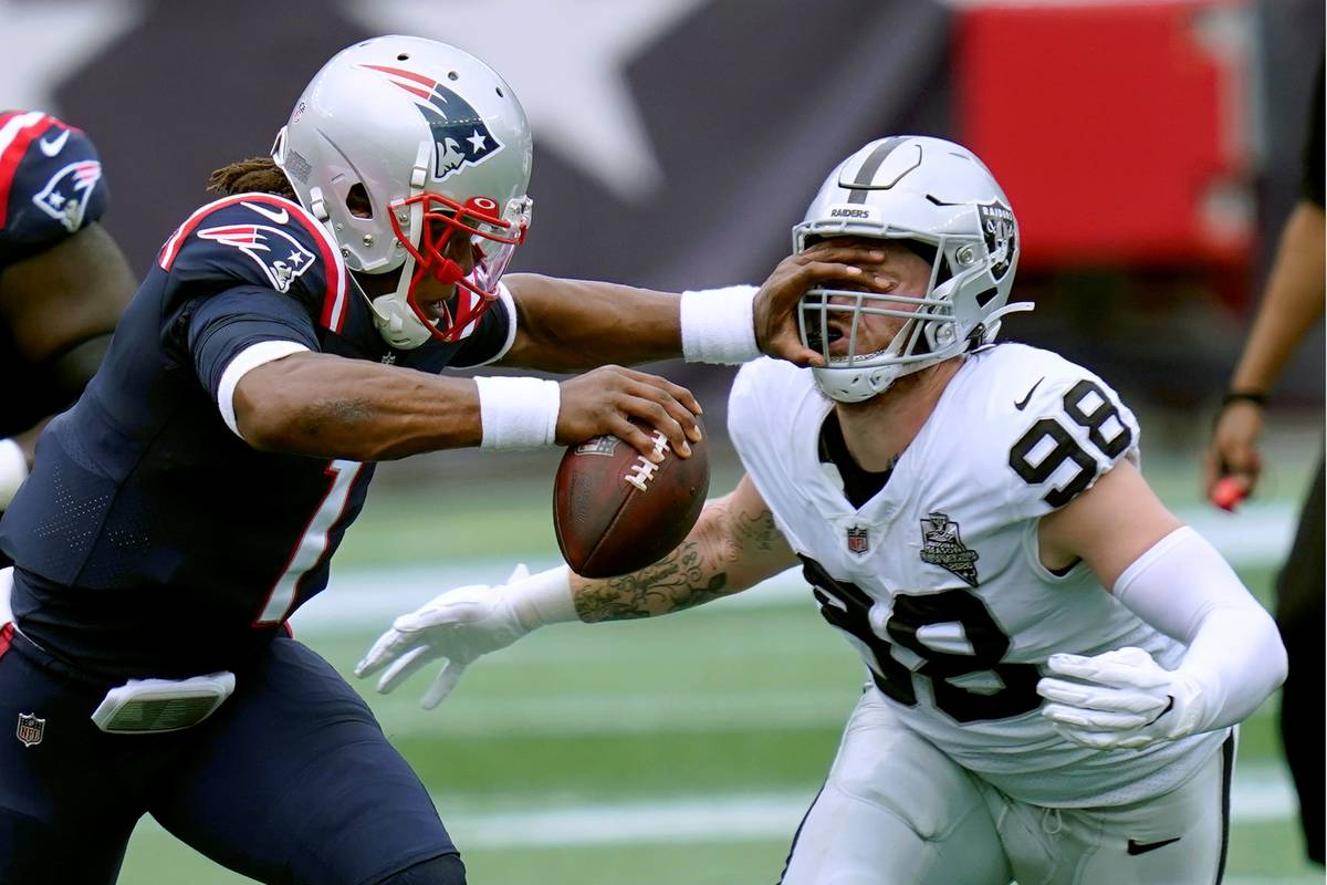 Las Vegas Raiders defensive end Maxx Crosby (98) gets a poke in the eye as he closes in to sack ...