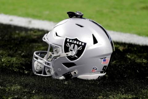 A Las Vegas Raiders helmet sits on the field prior to an NFL football game against the New Orle ...