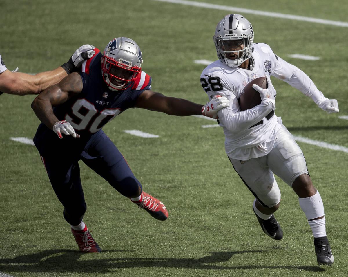 Las Vegas Raiders running back Josh Jacobs (28) turns the corner around New England Patriots li ...