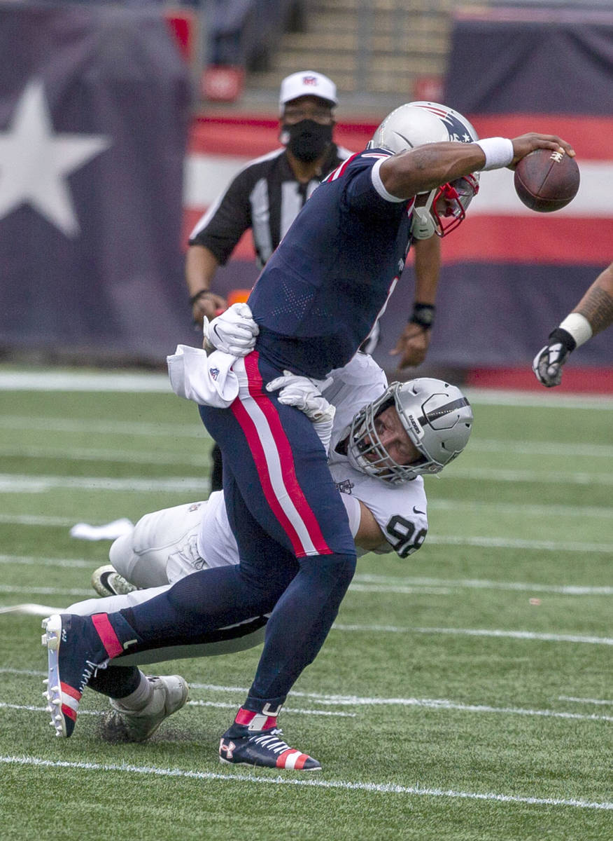 Las Vegas Raiders defensive end Maxx Crosby (98) wraps up New England Patriots quarterback Cam ...