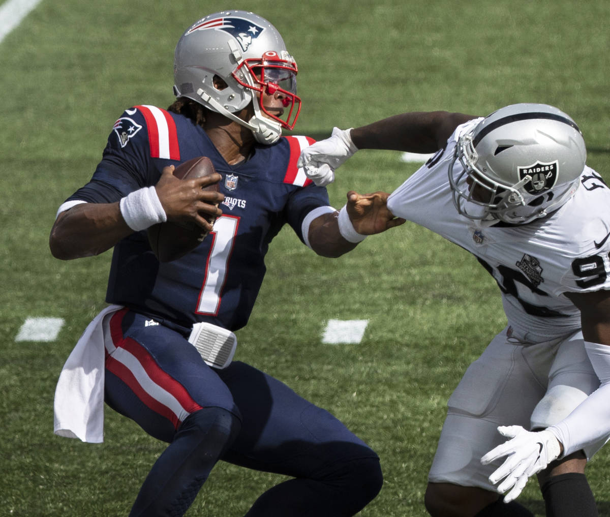 New England Patriots quarterback Cam Newton (1) stiff arms Las Vegas Raiders defensive end Clel ...