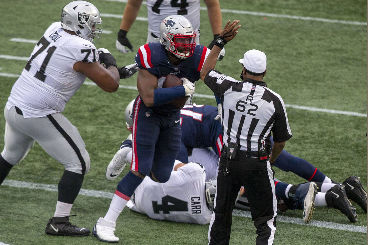 Las Vegas Raiders quarterback Derek Carr (4) is sacked in the end zone by both New England Patr ...
