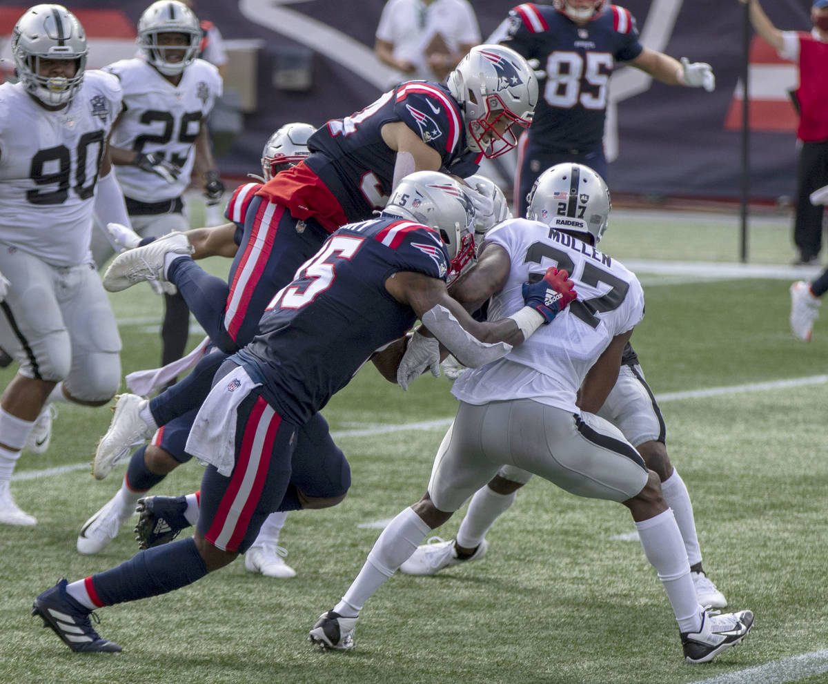 New England Patriots running back Rex Burkhead (34) leaps over Las Vegas Raiders cornerback Tra ...