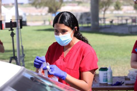 Registered nurse Liliana Sandoval explains a self-administered COVID-19 test to a patient at th ...