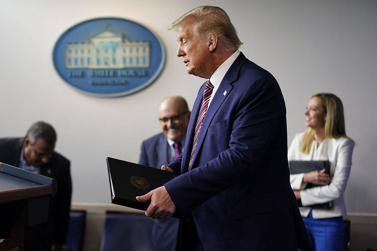 President Donald Trump walk towards the podium to begin speaking during a news conference at th ...
