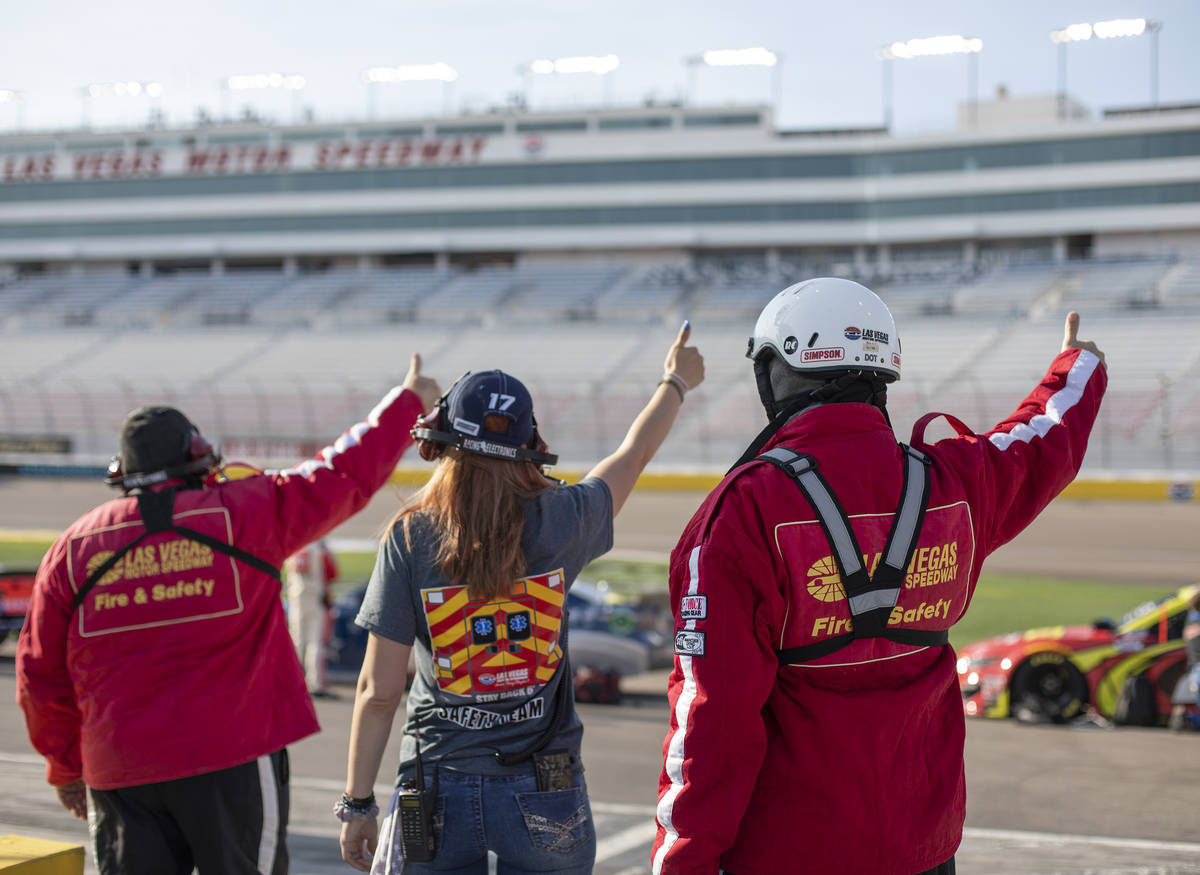 The pit fire safety team gives the okay for the race to begin beforea NASCAR Cup Series a ...