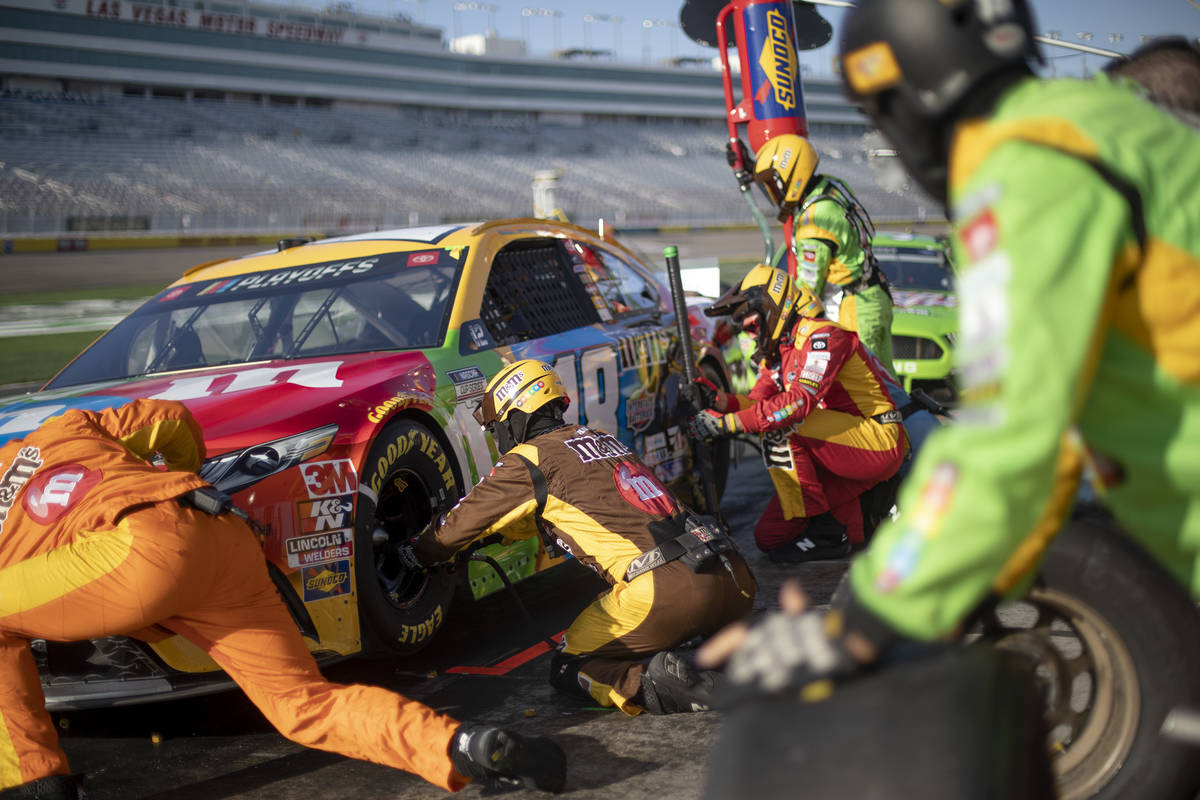The pit crew for Kyle Busch (18) runs out to service the car duringa NASCAR Cup Series au ...