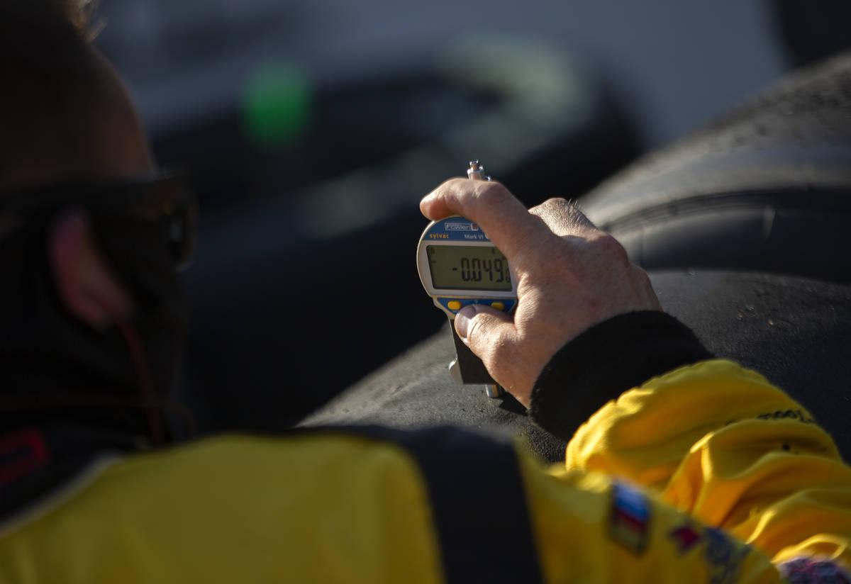A member of Michael McDowell's (34) pit crew checks tire pressure duringa NASCAR Cup Seri ...