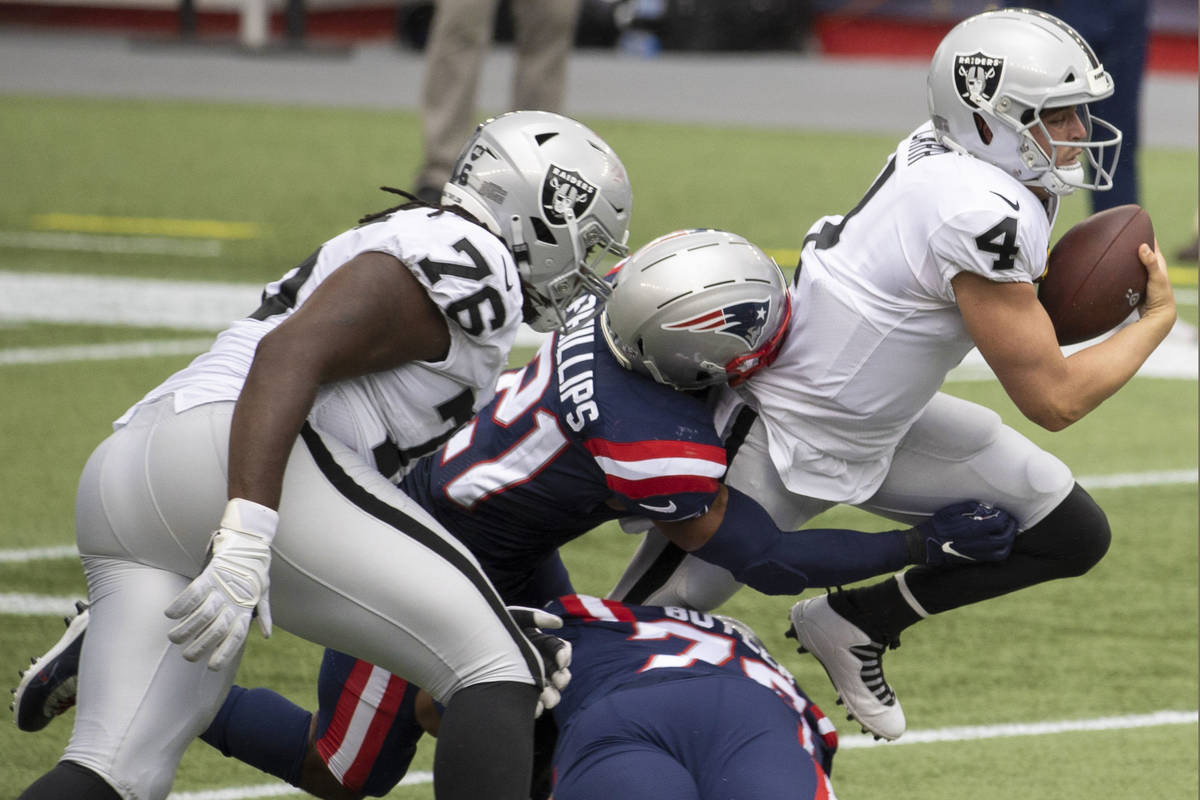 Las Vegas Raiders quarterback Derek Carr (4) is tackled for a loss by New England Patriots defe ...