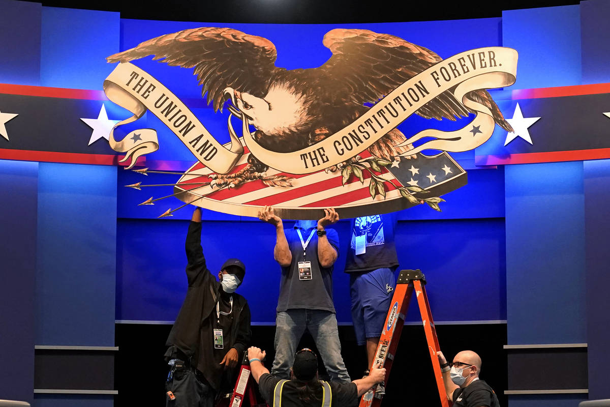 Workers adjust signage as preparations take place for the first Presidential debate in the Shei ...
