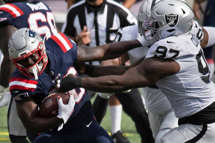 New England Patriots running back Sony Michel (26) tries to break free from Las Vegas Raiders d ...