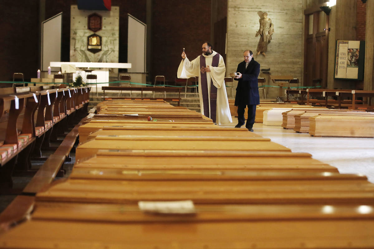 FILE - In this March 28, 2020, file photo, Don Marcello Crotti, left, blesses the coffins with ...